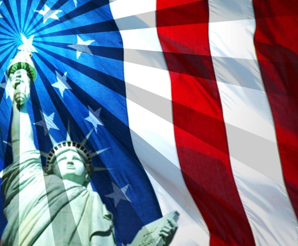 Statue of Liberty in front of flag